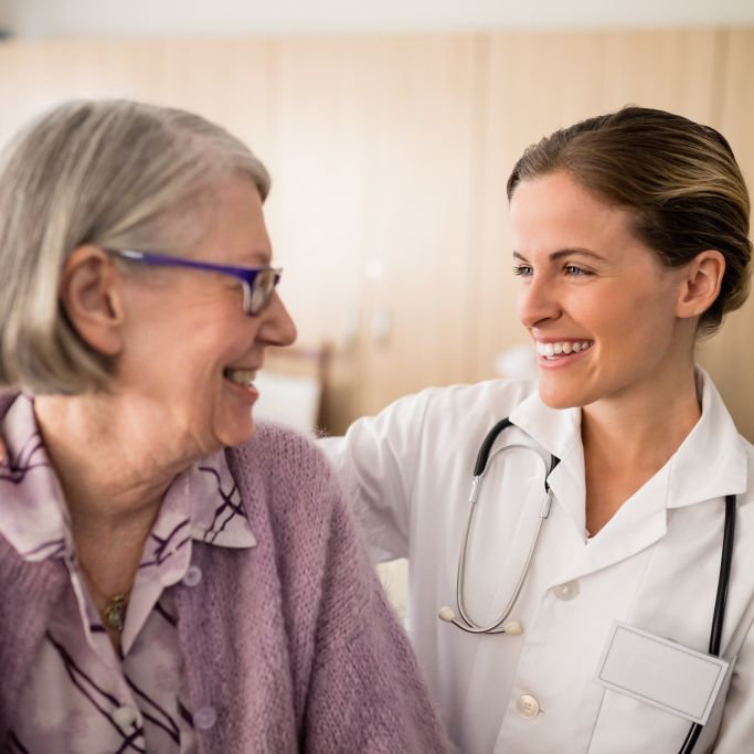 Smiling female doctor looking at senior woman with arm around in retirement home